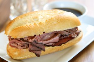 Roast beef in a long roll sitting on a white tray in front of a bowl of gravy.